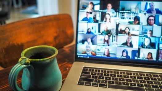 Online student chat with coffee mug next to laptop screen