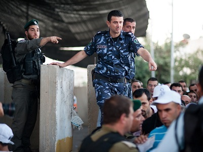 PA police coordinate with Israeli border police to control Palestinian access to Jerusalem at the Bethlehem checkpoint. (Photo: ActiveStills.org)