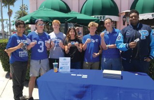 Football mom Lisa Taitelman (center) joined Palisades High School football team members (left to right) Kian Farahdel, Jared Dodson, Jack Estabrook, Theo Shulsky, Jonah Manheim and Syr Riley to sell discount cards to raise money for the football program.
