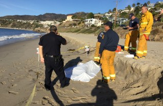 A woman's body found on the beach in Pacific Palisades on Jan. 13 is cordoned off by police.