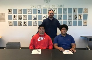 SMC Head Football Coach Kelly Ledwith (Standing) with Rick Kitamura and Marvin Williams. Both players signed full ride scholarship letters of intent. Credit: http://www.smccorsairs.com/sports/fball/2017-18/releases/20180202gg1toe