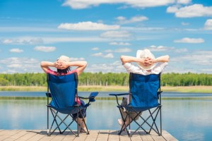 man and woman relax on a pier near a lake sitting on chairs