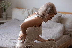woman experiencing back pain while sitting on bed