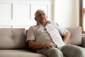 older man leaning on couch, suffering from strong pain in back