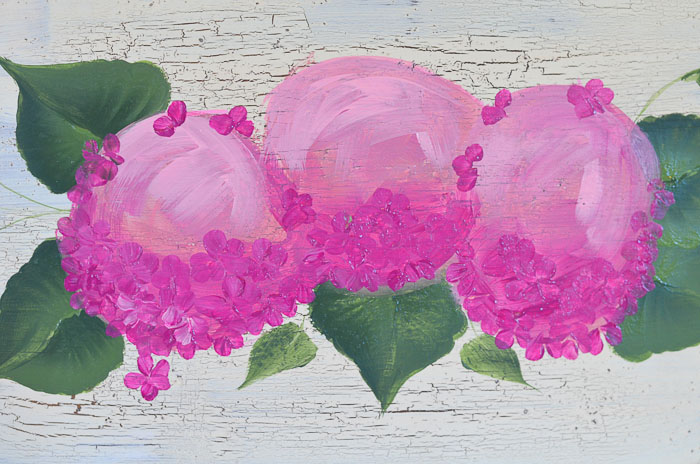 Dark petals being painting on pink hydrangeas