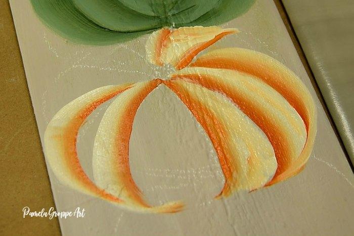 Painting the back ribs of a tiger pumpkin, Pamela Groppe Art