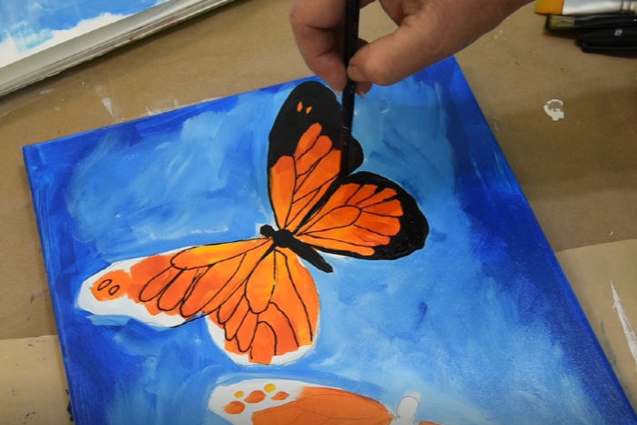 Paint outer edge of monarch butterfly wing with black paint