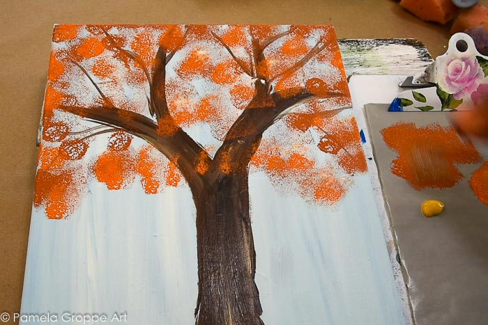 sponging terra cotta color paint onto tree