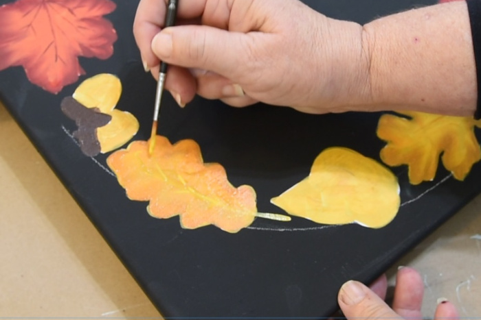 Adding veins to the smaller oak leaves with a liner brush.