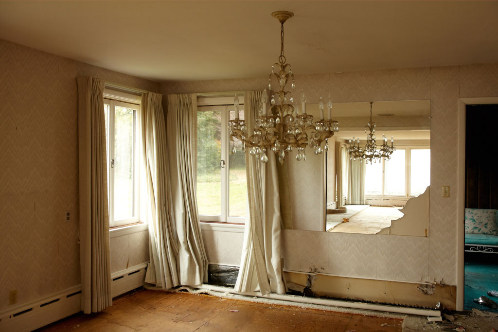A chandelier hangs in an empty ivory colored room and is reflected in a broken mirror.