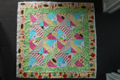 Because this is a smallish quilt (or blanket) there is no need to top stitch through all layers. On this one I have added the wadding to the back, and if you look closely, I have top stitched through both of the layers. This keeps the blanket looking neat and holding together well after many washes. There are many ways that you can top stitch on a quilt. I have just made quarter inch lines alongside the seams and it looks very tidy.