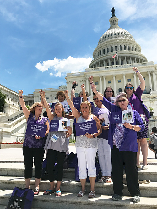 Pancreatic cancer advocates from Iowa raise their arms together in solidarity on the steps of the U.S. Capitol