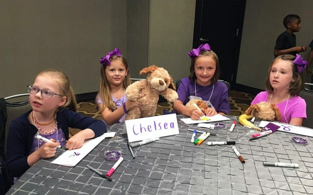 Four young girls wearing purple and holding stuffed PanCAN bears, color signs for National Pancreatic Cancer Advocacy Day