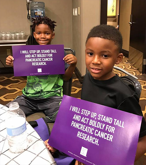 Two young boys smile while holding signs saying they will step up, stand tall and act boldly for pancreatic cancer research