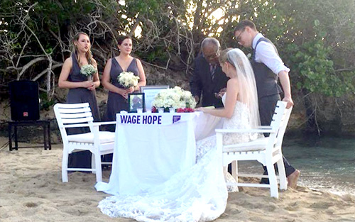 After beachside wedding ceremony, couple sign marriage license at table with Wage Hope banner supporting the cause.