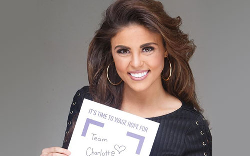 Miss Louisiana holds a Wage Hope sign for her PurpleStride team in honor of her grandmother