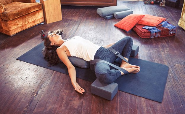 Lauren Eckstrom lies in yoga pose with feet together and pillows supporting areas of tension