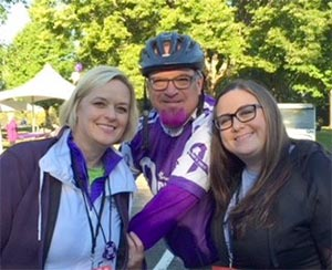 Longtime pancreatic cancer survivor with her husband and daughter at PurpleRideStride event