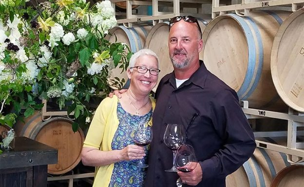 Pancreatic cancer patient and her husband stand before several barrels of their wine company.