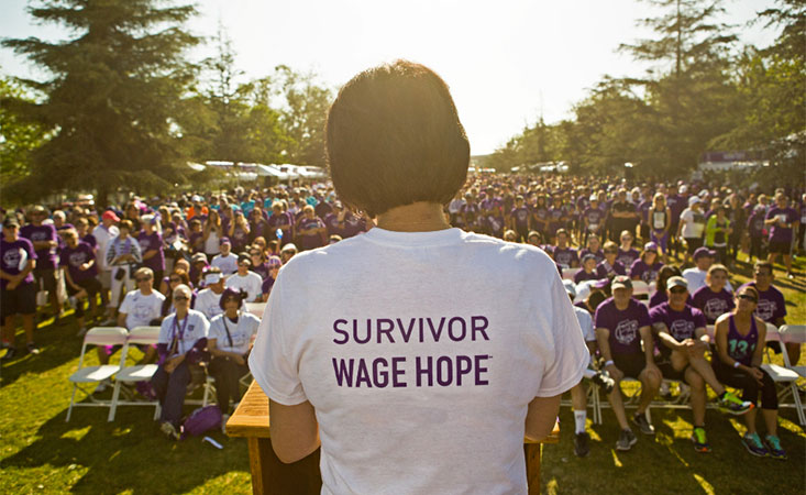 "A woman speaks for the pancreatic cancer cause in a shirt that reads ""Survivor: Demand Better"""