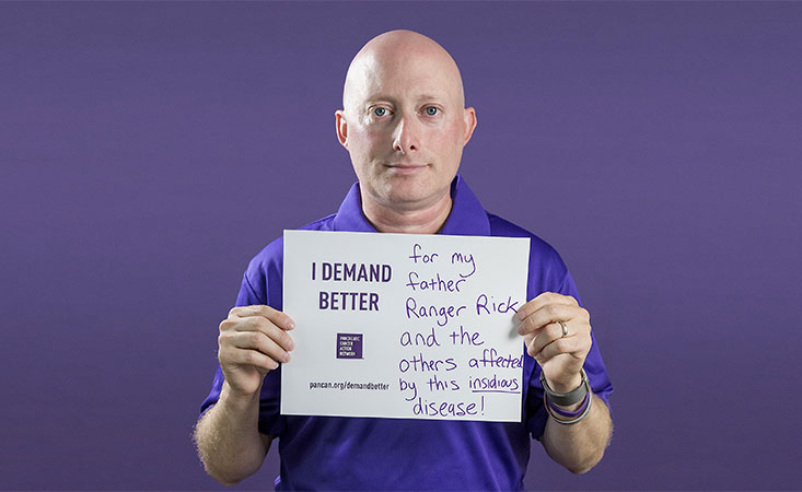 Volunteer and advocate holds a sign saying why he Demands Better for pancreatic cancer patients