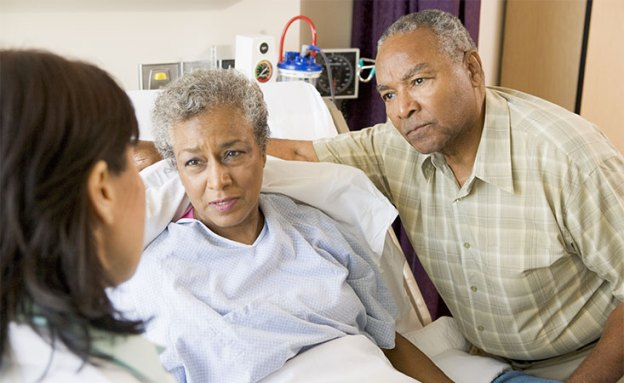 Pancreatic cancer patient supported by her caregiver speak with their doctor at the hospital