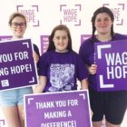 High schooler and her two friends holding signs of hope at the walk to end pancreatic cancer