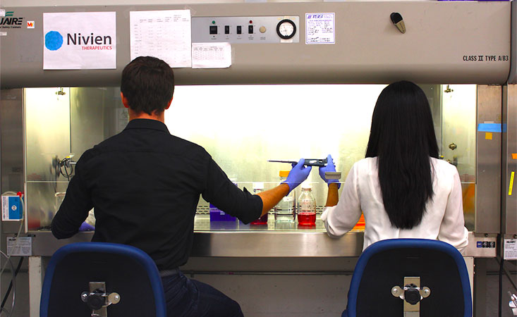 Co-founders of Nivien Therapeutics share a pipette in lab to test a new pancreatic cancer drug