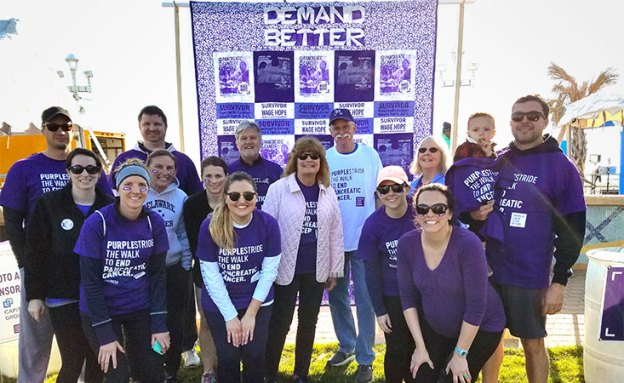 Pancreatic cancer survivor and PurpleStride fundraising team stand next to homemade quilt