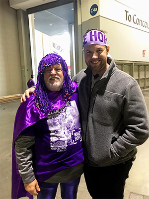 Man wearing purple wig volunteers at PurpleStride walks nationwide to end pancreatic cancer