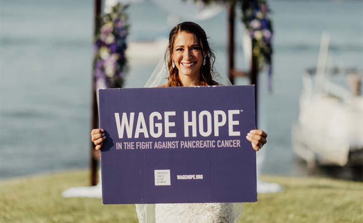 """Bride holds a pancreatic cancer """"Wage Hope"""" sign at her wedding to honor her late father"""