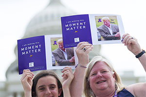 Mom and daughter show photo at Capitol building of family member who died of pancreatic cancer