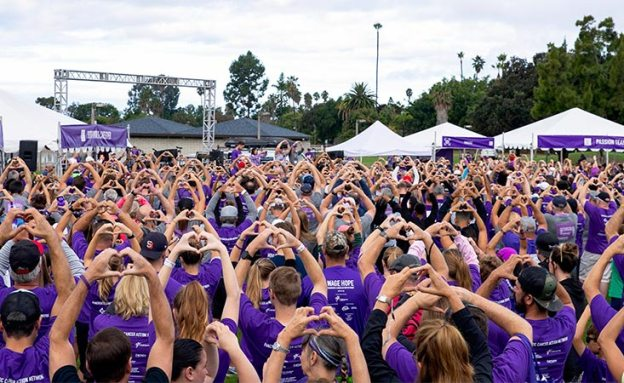 San Diego PurpleStride attendees hold hands up in heart-shaped gesture at pancreatic cancer walk