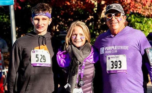 Woman and man with teenage boy at charity fundraiser walkathon.