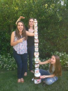 3 young Caucasian women with jars of Nutella stacked tall next to them.