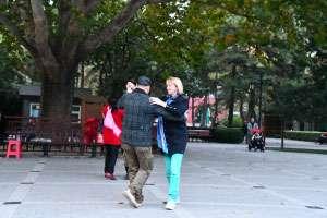 Caucasian woman dancing in Chinese neighborhood.