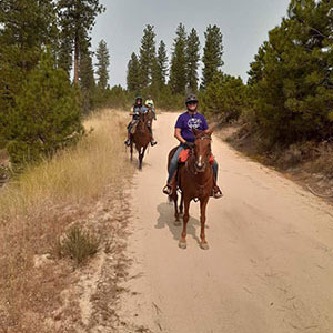 Two PurpleStride participants ride their horses.