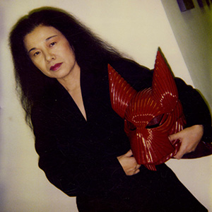 Eiko Ishioka holding a red costume piece from the movie The Cell.
