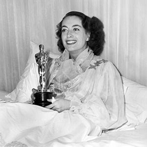 Black and white photo of Joan Crawford accepting her Oscar in bed.