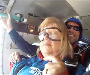 Middle-aged Caucasian female getting ready to skydive from plane with 30s Caucasian male behind her