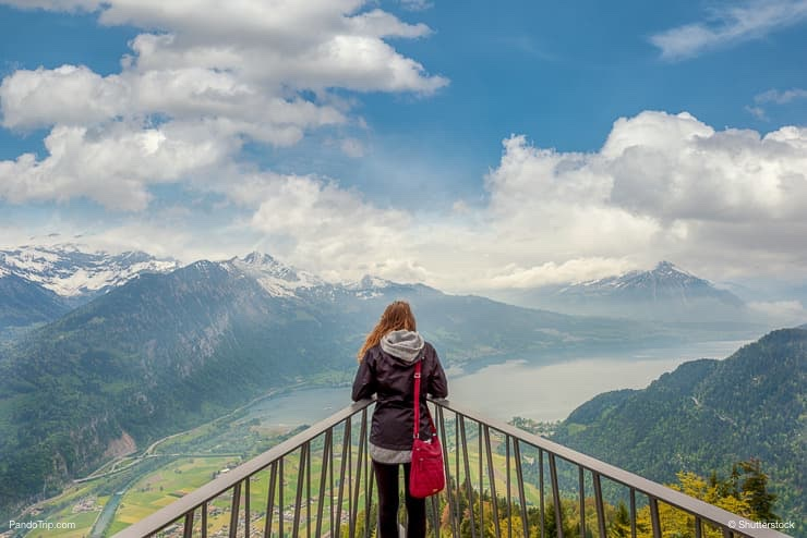 Woman looking to Interlaken panorama from viewpoint at Harder Kulm