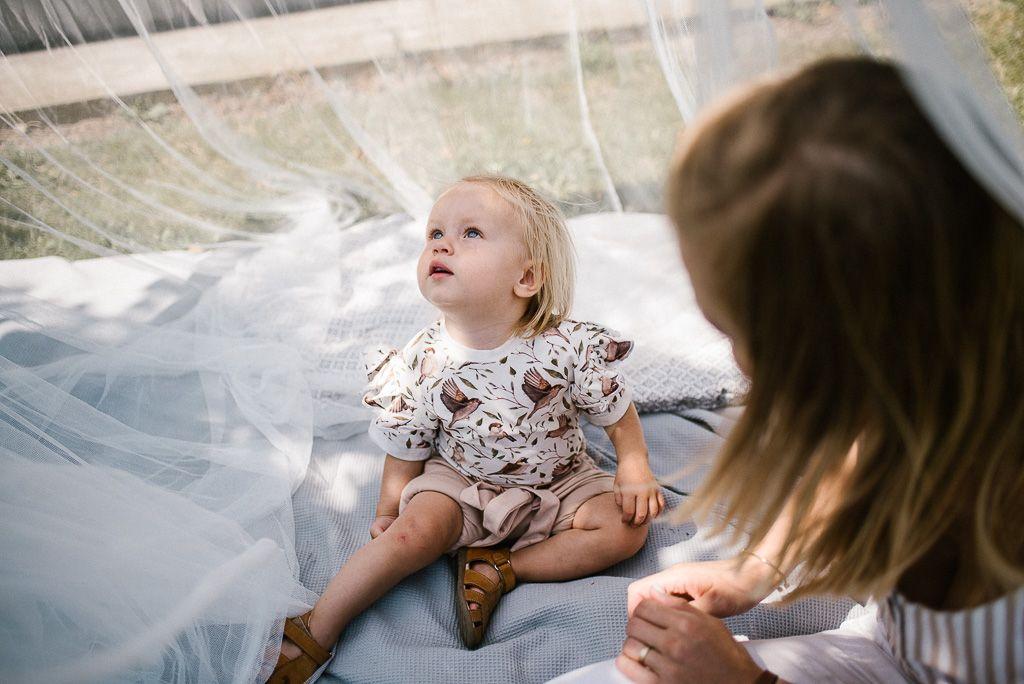 Dziewczynka siedzi na kocu i patrzy do góry na pikniku boho