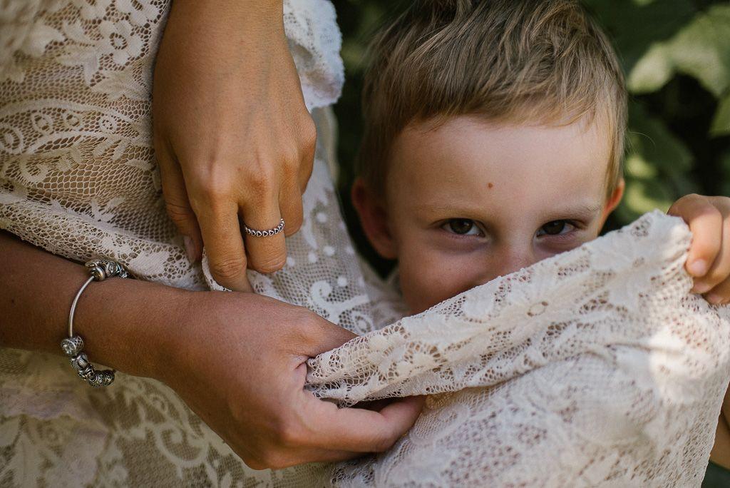 Chłopiec chowa się na koronkową sukienką boho mamy