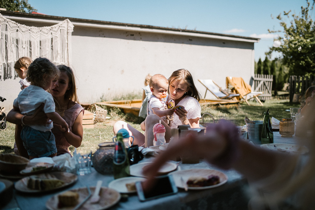 Dziewczyny z dziećmi siedzą przy stole na pikniku urodzinowym boho