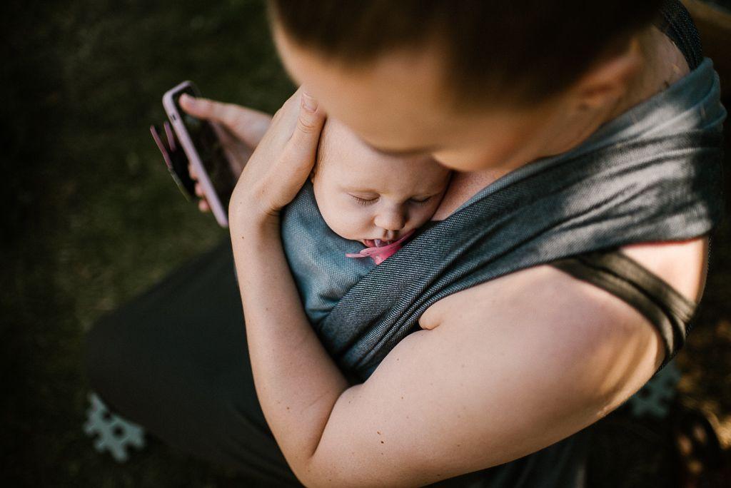 Mama trzyma maleństwo w chuście na pikniku boho
