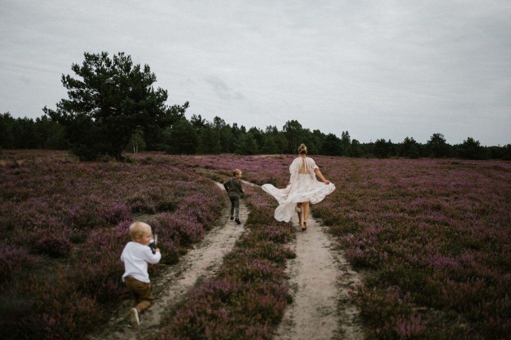 Mama z synami ucieka przez wrzosowisko - sesja zdjęciowa na wrzosowisku Pani Woźna