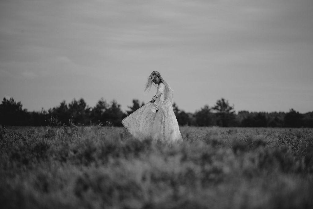 Kobieta tańczy w sukni ślubnej koronkowej na wrzosowisku - sesja zdjęciowa na wrzosowisku Pani Woźna