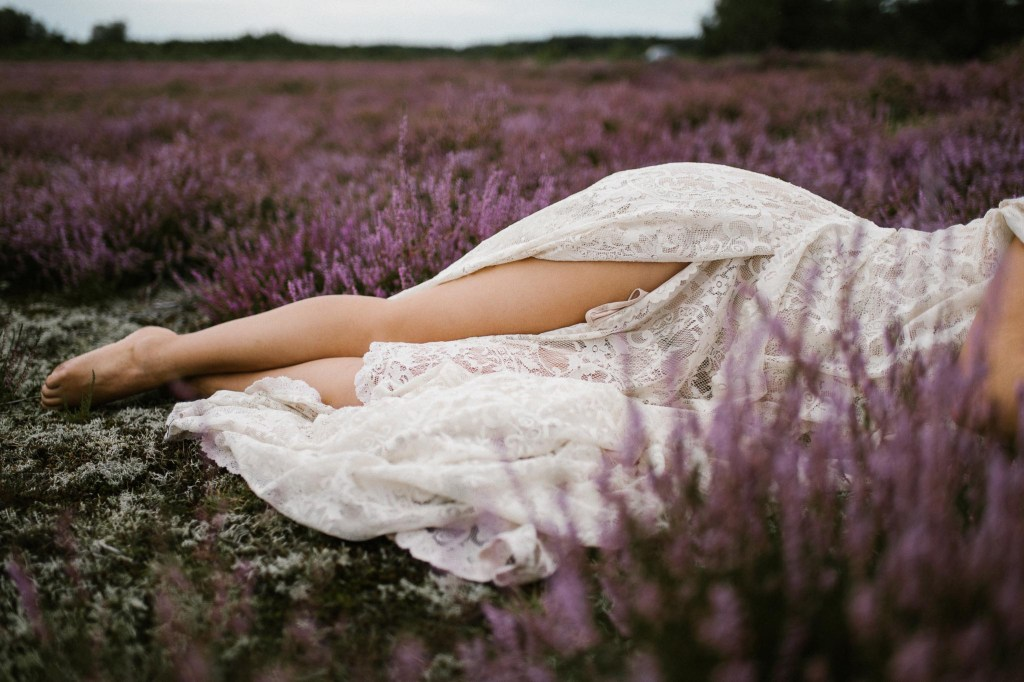 Kobieta w sukni ślubnej leży na wrzosowisku - sesja zdjęciowa na wrzosowisku Pani Woźna
