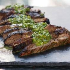 Sliced Skirt Steak topped with vibrant green Chimichurri sauce