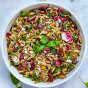 orzo pasta salad in a white bowl with a sprig of basil in the middle
